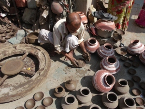 Punja Bhai demonstrating how to press clay to create ceramic pots.